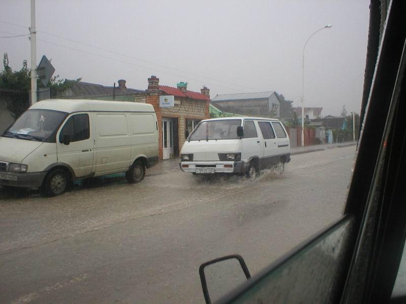 Дворники не успевают убирать воду со стекла, а поток на улице доходит почти до дверей
